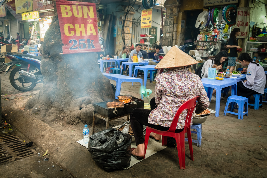 A Vietnamese woman makes street food in Hanoi, Vietnam. Photo by Barbara Cameron Pix, Food & Travel Photographer
