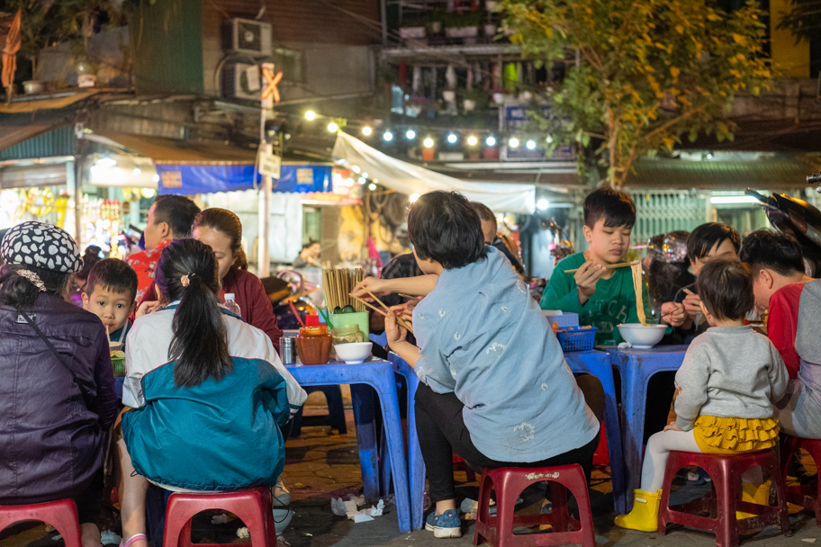 Family sitting at a street pho restaurant in Hanoi, Vietnam. Photo by Barbara Cameron Pix, Food & Travel Photographer