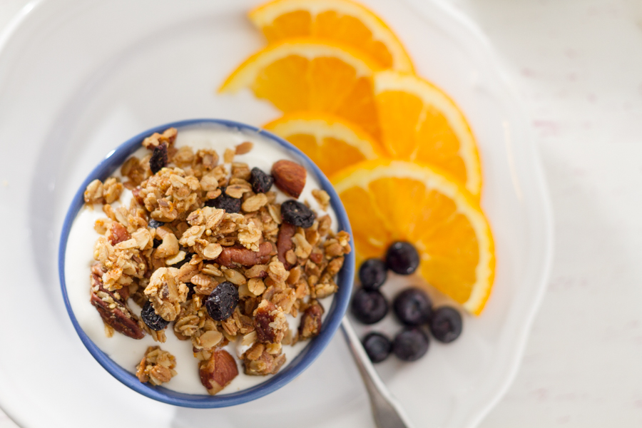 bowl of homemade granola with blueberries and yogurt and orange slices