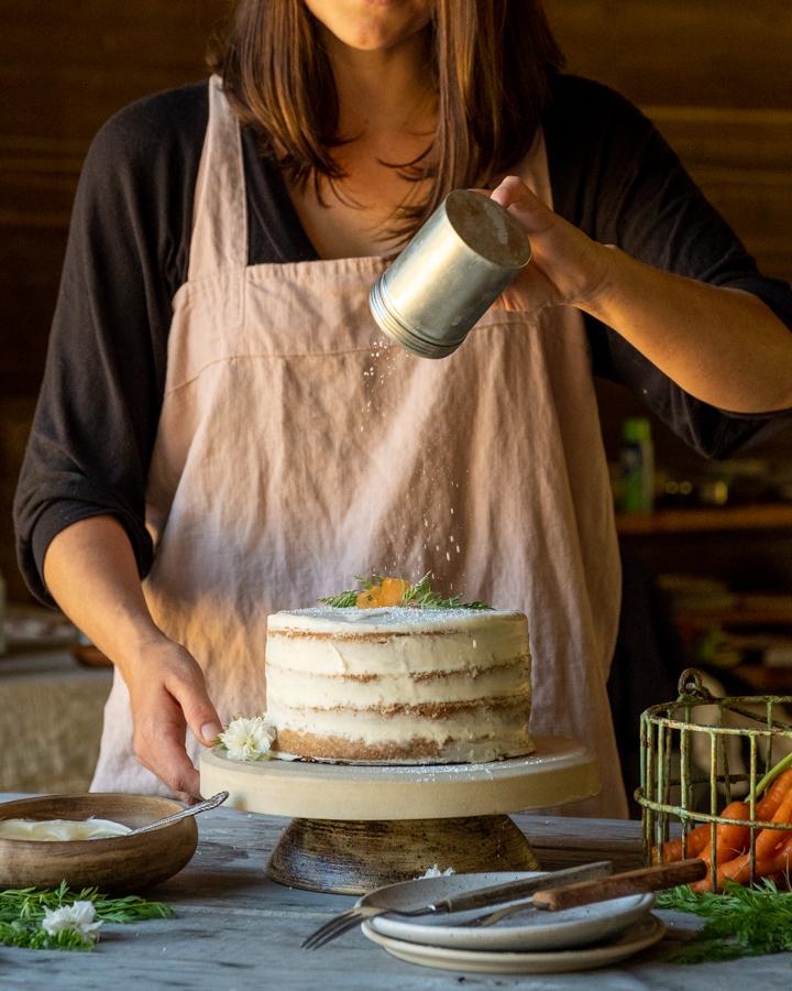 woman sprinkling icing sugar on carrot cake food photography