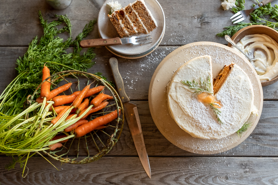 carrot cake with cream cheese frosting with sprinkled icing sugar and basket of fresh carrots food photography