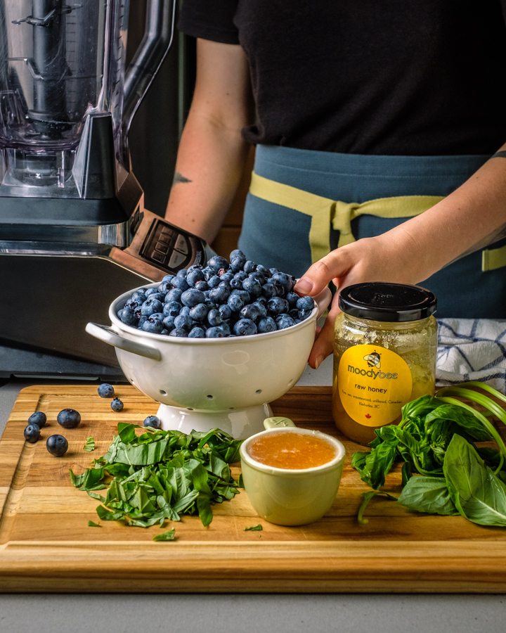 chef preparing blueberries and basil and honey to make popsicles