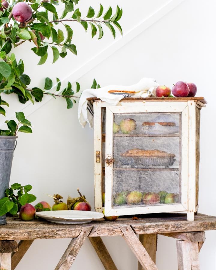fresh apple pies in a farmhouse cupboard beside an apple tree