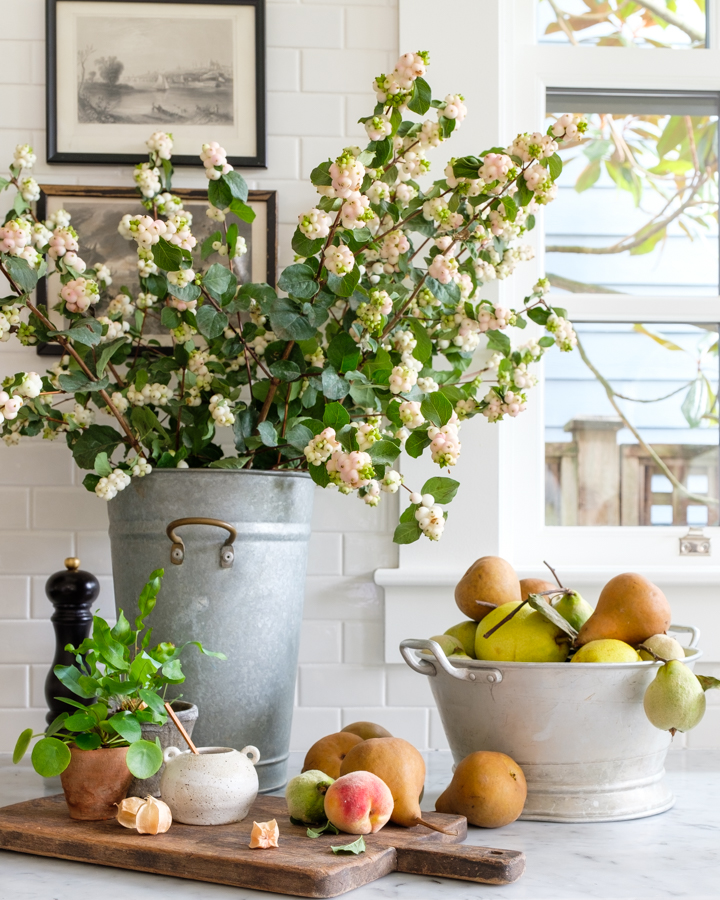 pears and peaches in a bucket and on a cutting board with a bucket of fresh flowers- food photography by barbara cameron