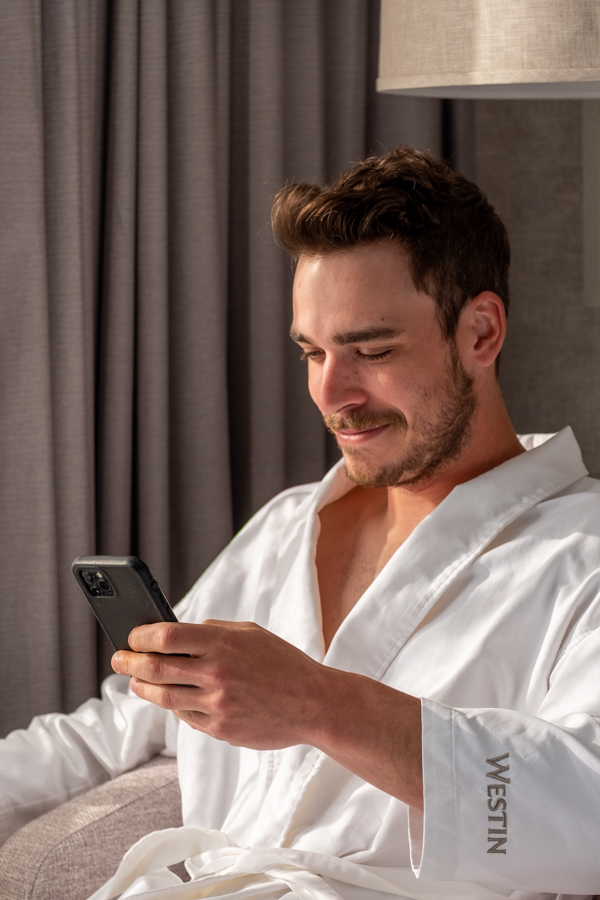 man in hotel robe looking at iphone   Barbara Cameron Pix